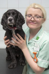 Veterinary Nurse smiling at camera while holding black dog