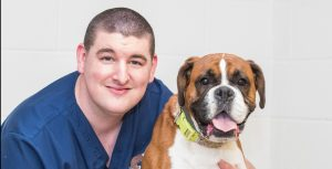 Colin Jordan Head Nurse at Border Vets with boxer dog in practice