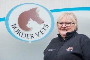 Maggie Gormon Receptionist at Border Vets next to sign for vets in Selkirk